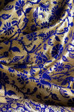 Blue and gold fabric. Detail image of blue and gold fabric making folds with flowers and paisleys Stock Images