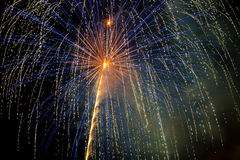 Blue Gold Fireworks. Blue and gold fireworks explode and rain down on the Fourth of July with a background of an inky black and smoky night sky Royalty Free Stock Photos