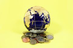 Blue and gold globe sitting on top of a pile of a mixture of coins from the US Europe and Britain Stock Photos