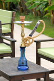 Blue and gold hookah on the table of an outdoor cafe. Stock Photo
