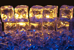 Blue and Gold Ice. Blue and Gold Illuminated Ice Cubes on a Isolated Black Background Royalty Free Stock Photography