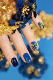 Blue and gold manicure. Multicolored manicure with blue nail Polish decorated with rhinestones different shapes with festive decorations royalty free stock images