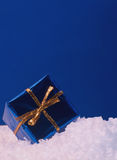 Blue and gold present. Blue present with gold bow on snow with blue back ground Stock Image