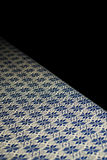 Blue and gold traditional Thai tablecloth over black background Royalty Free Stock Photo