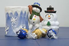 Blue and gold truffles. Winter season table scene tabletop of a blue tablecloth against a white background with colorful colourful plastic white snowman with royalty free stock photography