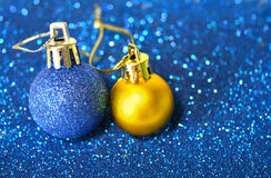 Blue and golden Christmas balls on blurry background of blue glitter Royalty Free Stock Photo