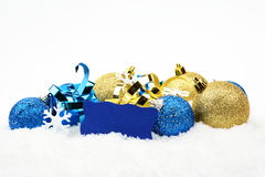 Blue,golden christmas decoration in line on snow with wishes card. Decoration of blue and golden christmas baubles and gifts in line with wishes card on snow royalty free stock photos