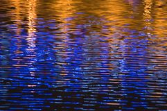 Blue and golden waves. Reflection of neon ad lights in waves of a river making colourful pattern Royalty Free Stock Images
