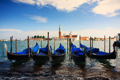 Blue gondolas in Venice. A group of blue gondolas in Venice, in the background the island of St George Royalty Free Stock Image