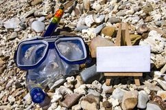 Blue googles for snorkeling or swimming and white canvas for travel activities concept. On the beach at sunny day. selective focus shot Stock Images