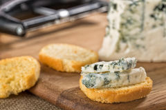 Blue gorgonzola cheese slices on crusty bruschetta Royalty Free Stock Image