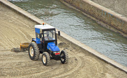 Blue grader tractor. Waiting to clean the beach sand stock photos