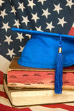 Blue graduation cap on books. Bright blue graduation cap on old books with American flag background Stock Photos