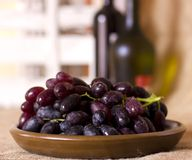 Blue grapes on a clay brown dish. Blue grapes on the clay brown dish Stock Images