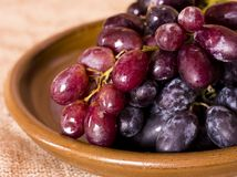 Blue grapes on a clay brown dish. Blue grapes on the clay brown dish Stock Photo