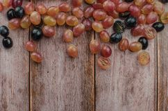 Blue grapes with green leaf healthy eating, isolated. On wood background stock photography