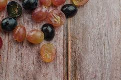 Blue grapes with green leaf healthy eating, isolated. On wood background stock images
