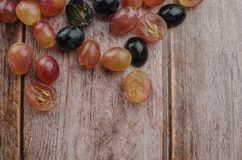 Blue grapes with green leaf healthy eating, isolated. On wood background royalty free stock image
