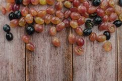 Blue grapes with green leaf healthy eating, isolated. On wood background stock image