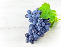 Blue grapes with green leaf on wooden board Royalty Free Stock Photography