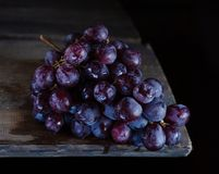 Bunch of grapes lies on a wooden table stock images
