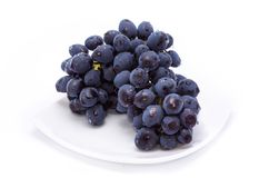 Blue grapes on a white plate stock photos
