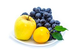 Blue grapes with yellow apple and lemon on a white plate stock photography