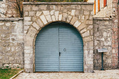 A blue-gray metal gate in a stone fence Royalty Free Stock Image