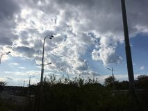 Blue-gray sky, dark clouds. Road, trees. Stock Photo