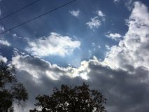 Blue-gray sky, sun through the clouds. Trees, wires. Vladivostok nature in early autumn Royalty Free Stock Images