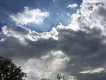 Blue-gray sky. Sun through the dark clouds, trees. Royalty Free Stock Photos