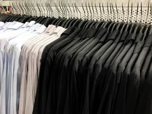 Blue, gray with white dot and black shirt on hangers in shopping. Blue, gray with white dot and black shirt on hangers and rack in shopping store Royalty Free Stock Images