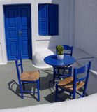 Blue Greek veranda. A small veranda of a Greek house with a blue table, chairs, a blue door and window shutters Royalty Free Stock Images