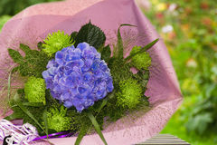 Blue and green bouquet of flowers. Wrapped in paper with summer garden background Royalty Free Stock Photos