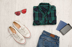 Blue-green checkered shirt, glasses, sneakers, jeans, phone and passport. Wooden background. Fashionable concept Royalty Free Stock Images