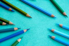 Blue and green colored pencils on a blue background. Blue and green colored  pencils scattered on a blue background Stock Photography