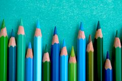 Blue and green colored pencils on a blue background. Blue and green colored pencils staggered at the bottom of the screen Royalty Free Stock Photography