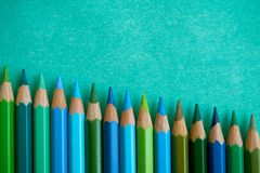 Blue and green colored pencils on a blue background. Blue and green colored pencils at the bottom of the screen Stock Photo