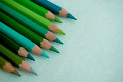 Blue and green colored pencils on a blue background. Blue and green colored pencils in the left corner of the screen Stock Photography