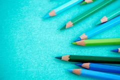 Blue and green colored pencils on a blue background. Blue and green colored pencils scattered on a blue background Royalty Free Stock Photography