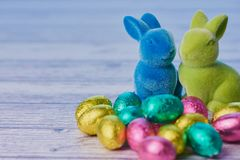 Blue and green easter bunnies beside colored chocolate eggs on white wooden background royalty free stock images