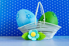 Blue and green Easter eggs in a basket with blue flower Stock Photos