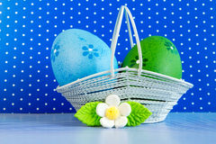 Blue and green Easter eggs in a basket with white flower Stock Image