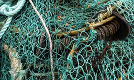 Green Fishing Net England. Blue and Green Fishing Net with ropes on a pile in Lymington, England stock image