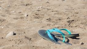 Blue and green flip flops. In the sand royalty free stock image