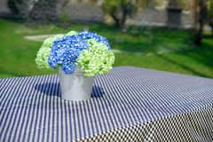 Blue and green flowers in bucket vase on table cover by table ma stock photo