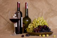 Blue and green grapes on a clay brown dish. Bottle with red and Royalty Free Stock Photo