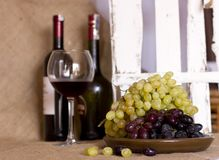 Blue and green grapes on a clay brown dish. Bottle with red and Stock Photo