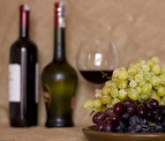 Blue and green grapes on a clay brown dish. Bottle with red and Stock Photography
