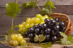 Blue and green grapes in a wicker basket on wooden table.  royalty free stock photos